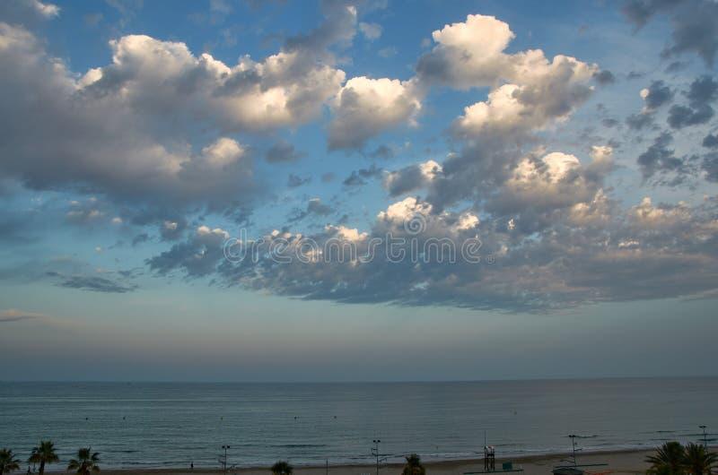 Nubes de tormenta al atardecer sobre el mar imagen de archivo
