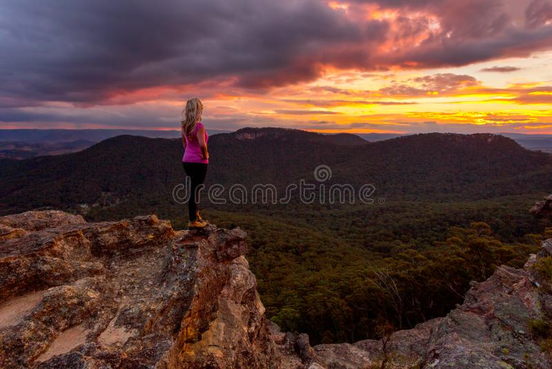 Nubes de tormenta de observación de la mujer sobre las montañas azules en la puesta del sol imagen de archivo libre de regalías