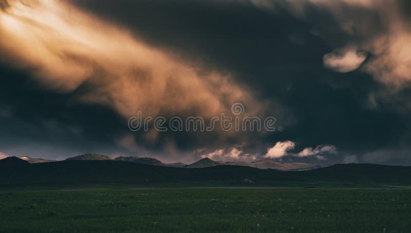 Nubes de tormenta oscuras sobre un prado imagenes de archivo