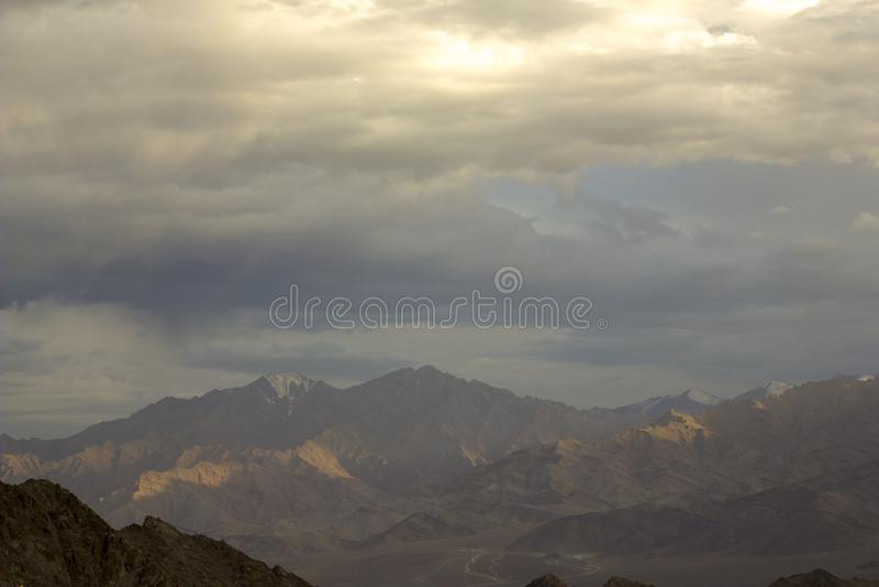 Nubes de una lluvia sobre un valle de la montaña con los picos nevosos foto de archivo libre de regalías