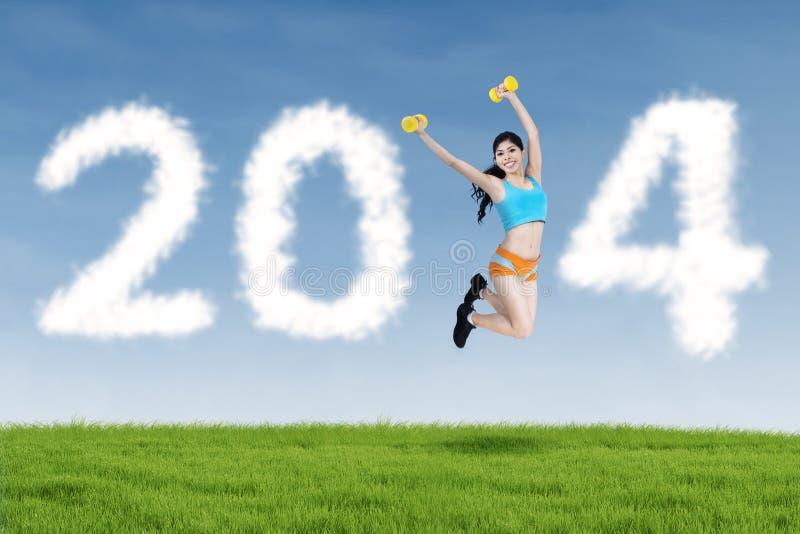 2014 nubes del Año Nuevo y salto de la mujer de la aptitud imágenes de archivo libres de regalías