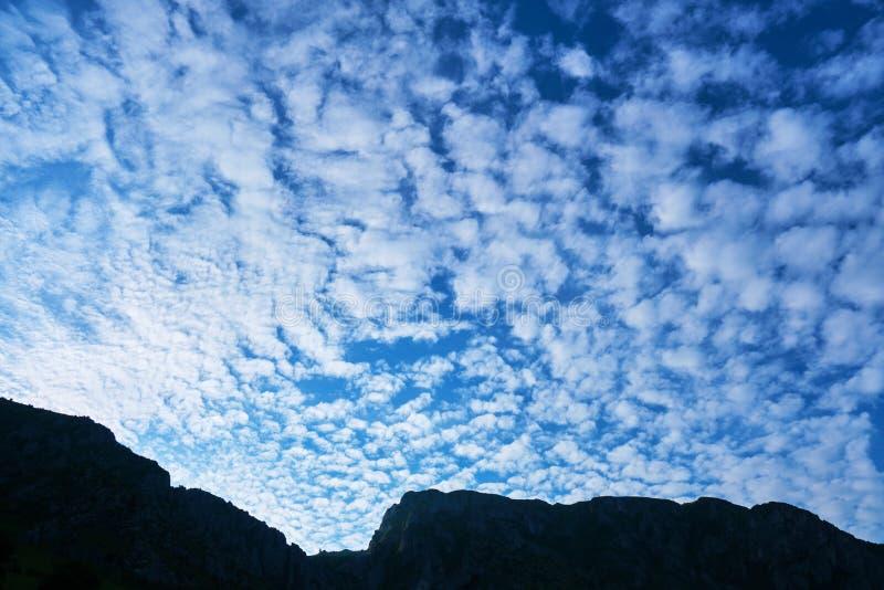 Nubes del floccus del Altocumulus, cielo azul de la mañana, y una silueta del canto de la montaña Ubicación: Pieza de las montaña imágenes de archivo libres de regalías