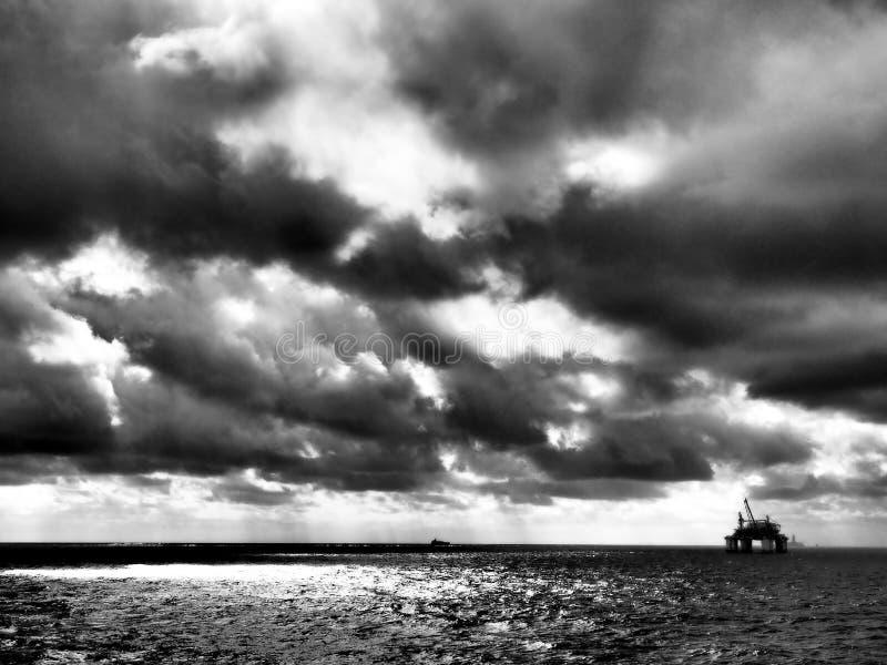Nubes dramáticas, blancos y negros de la plataforma petrolera costera imagen de archivo