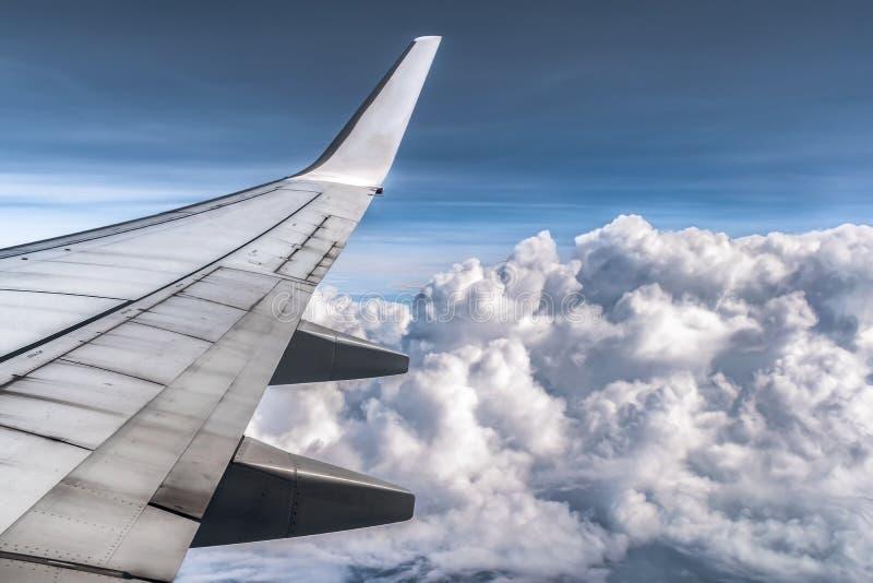 Nubes dramáticas de la ventana del aeroplano Las alas y todos los componentes son visibles Nubes mullidas como bolas de algodón imagen de archivo libre de regalías