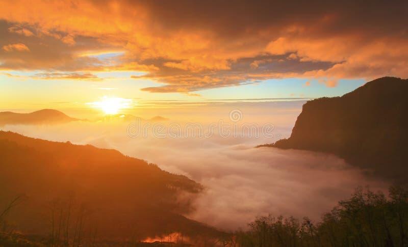 Nubes dramáticas que ruedan sobre las montañas en la puesta del sol imagen de archivo