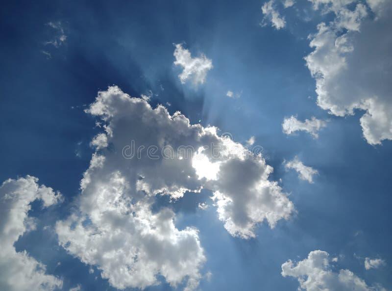Nubes en cielo azul con los rayos del sol imagenes de archivo