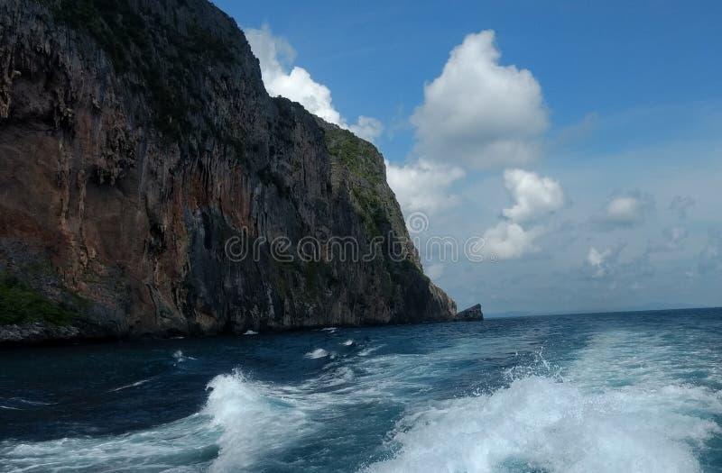 Nubes en el cielo azul con las olas oceánicas y la montaña, papel pintado del fondo fotografía de archivo libre de regalías