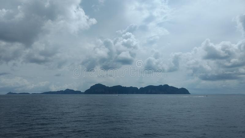 Nubes en el cielo azul con las olas oceánicas y las montañas, papel pintado del fondo fotografía de archivo