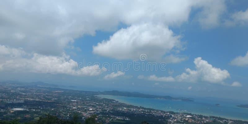 Nubes en el cielo azul con el océano, la ciudad y las montañas, papel pintado del fondo, paisaje fotografía de archivo libre de regalías