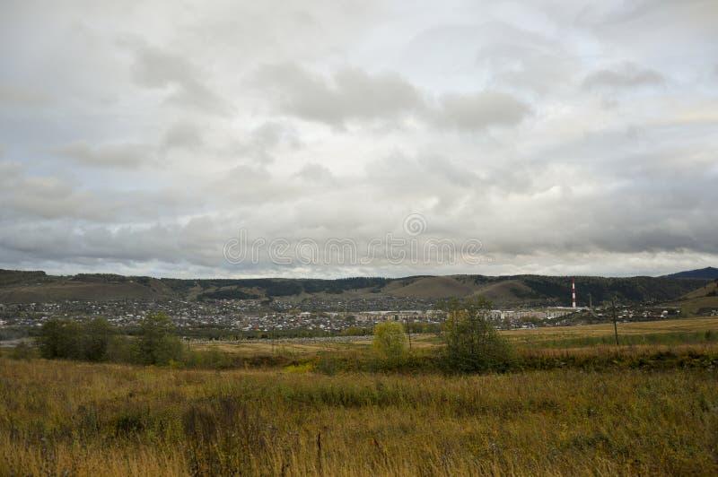Nubes grises pesadas en el cielo fr?o del oto?o sobre pueblo con las peque?as casas lejos en las monta?as y los campos travelling imagen de archivo libre de regalías