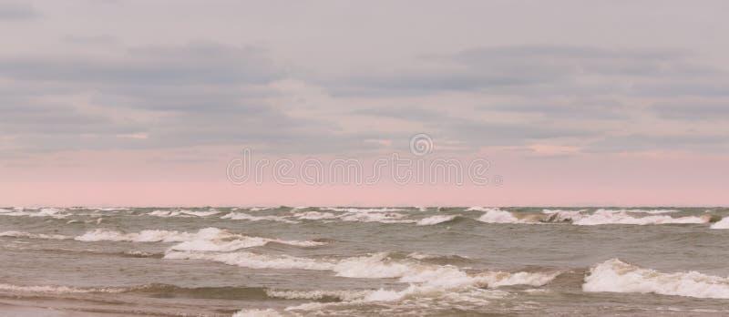 Nubes hermosas y cielo que brilla intensamente rosado sobre ondas picadas fotografía de archivo