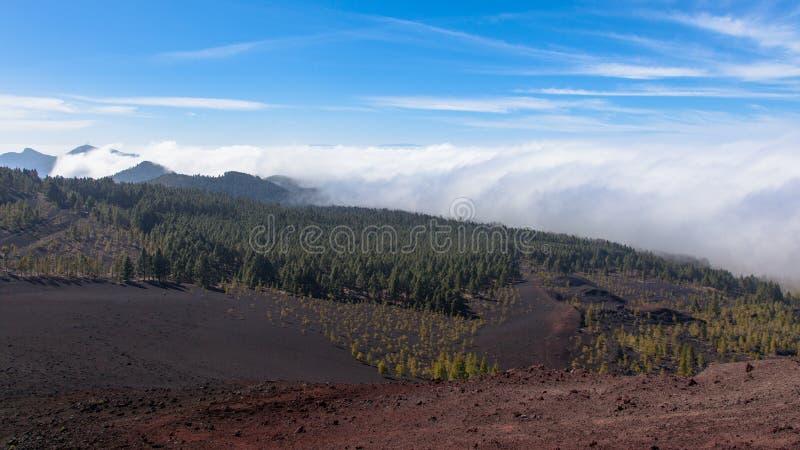 Nubes ornographic notables de la cascada que se derraman sobre la cuesta de sotavento de montañas en Tenerife septentrional imagen de archivo