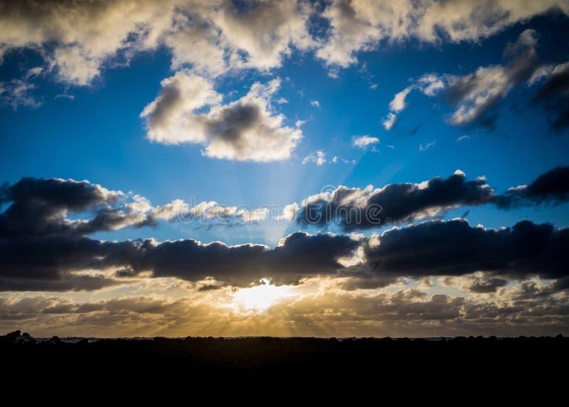 Nubes oscuras con los rayos del sol sobre el mar fotos de archivo