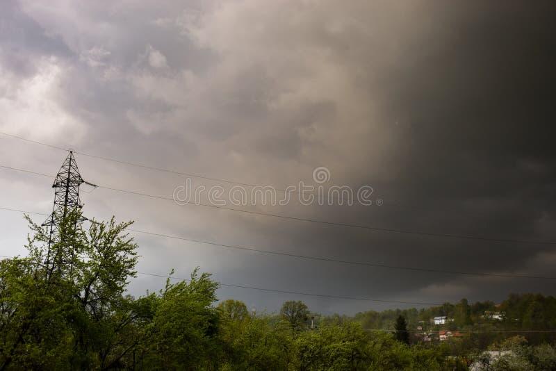 Nubes oscuras de la tormenta sobre el pueblo imagen de archivo