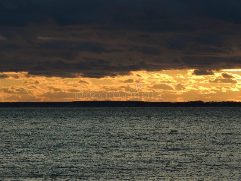 Nubes oscuras y puesta del sol sobre la costa foto de archivo