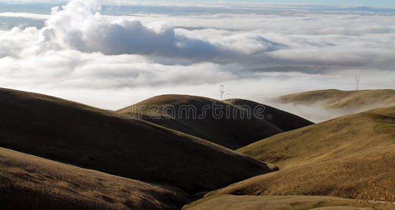 Nubes que cubren un valle de la montaña con Rolling Hills fotografía de archivo