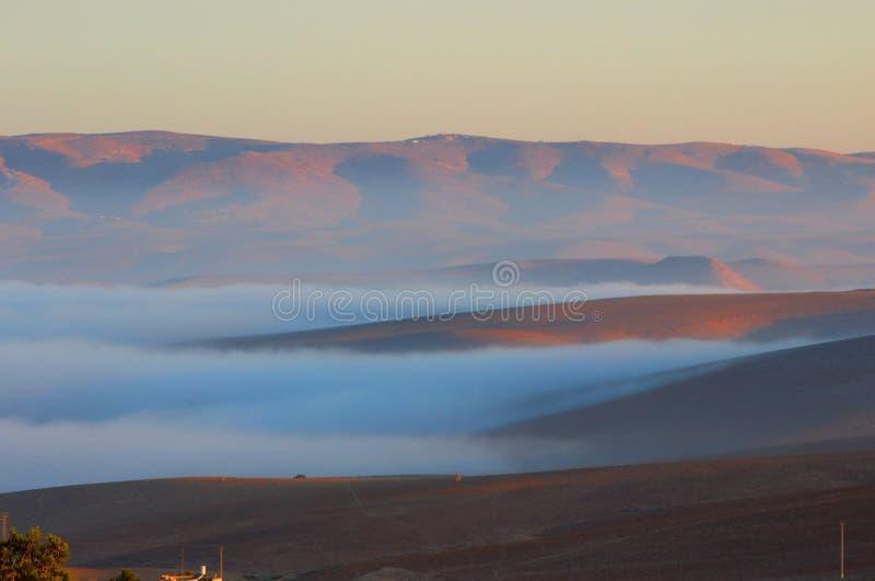 Nubes que vienen en las montañas rojas durante salida del sol en la ciudad Israel de Arad fotografía de archivo libre de regalías