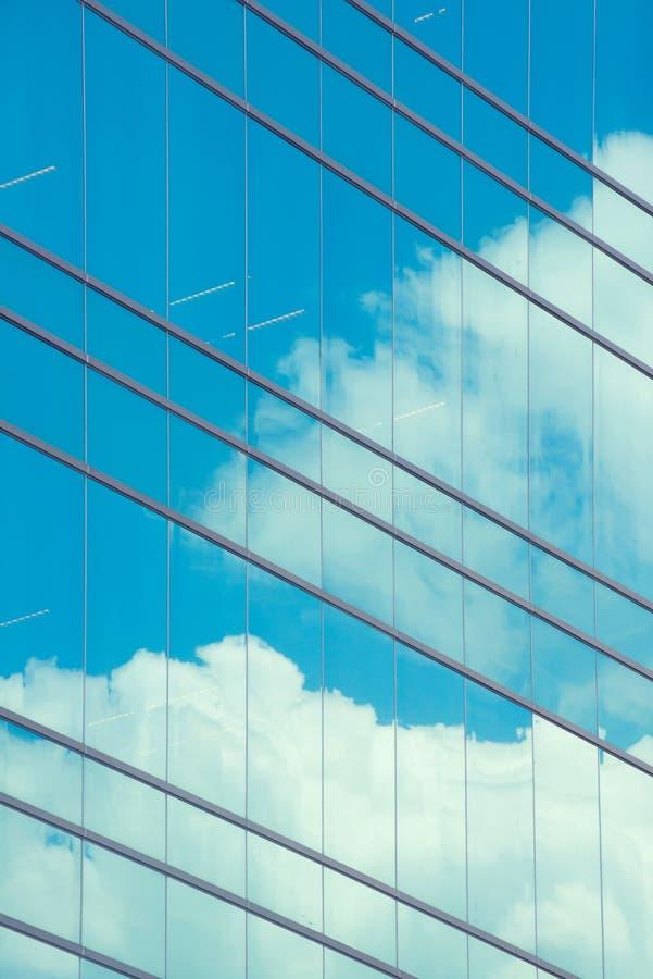 Nubes reflejadas en ventana moderna del edificio imagenes de archivo
