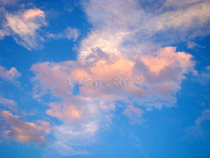 Nubes rosadas y blancas en Skey azul brillante foto de archivo