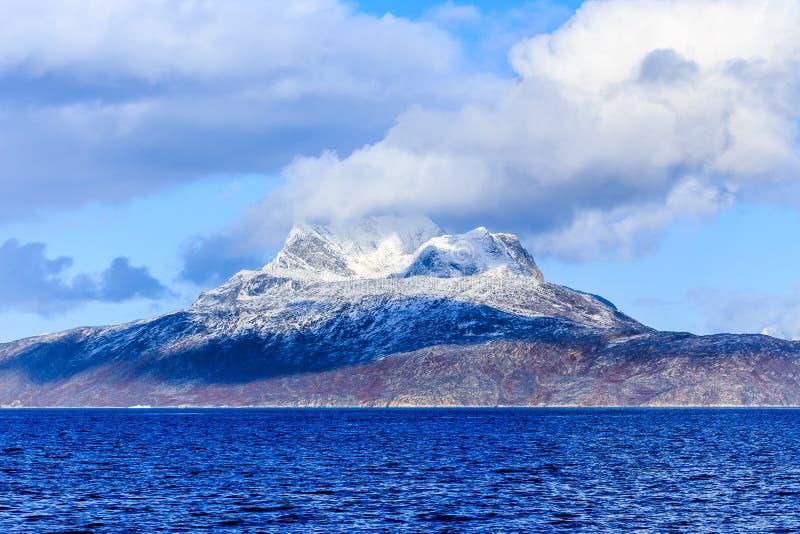 Nubes sobre la montaña de Sermitsiaq cubierta en nieve con el mar azul adentro foto de archivo