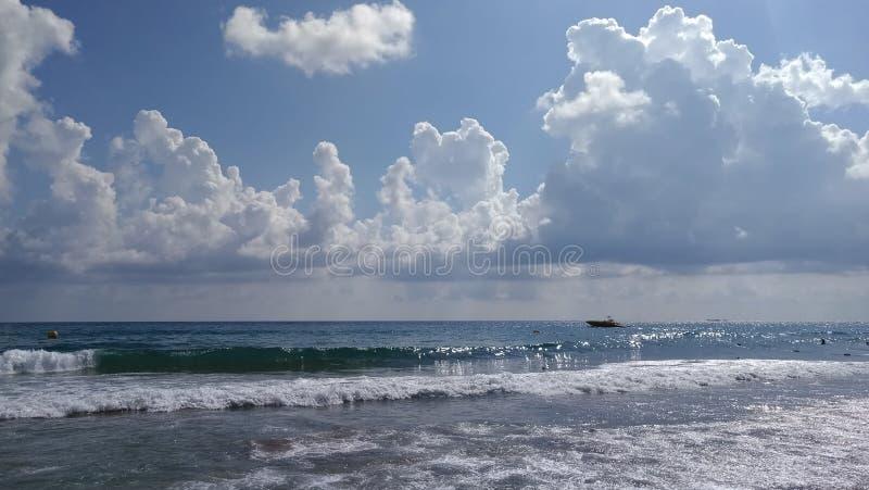 Nubes sobre las ondas del mar imagenes de archivo
