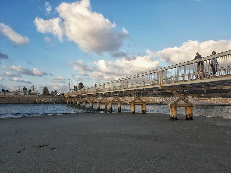 Nubes sobre un puente que cruza un río imagenes de archivo