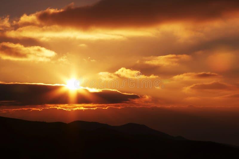 Nubes, sol y montaña en puesta del sol fotos de archivo