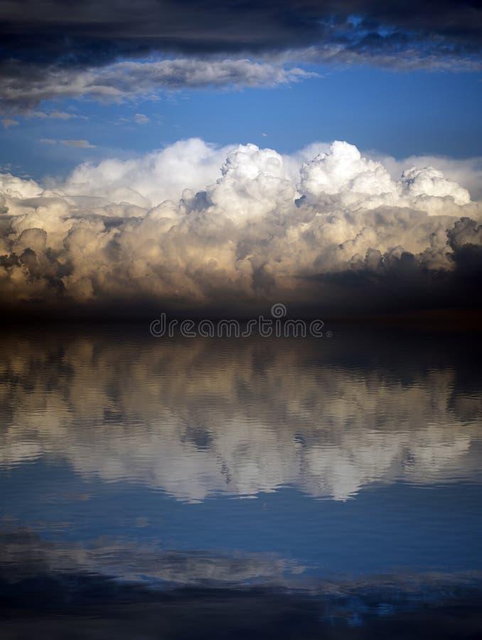 Nubes tempestuosas sobre el mar en la puesta del sol imagen de archivo