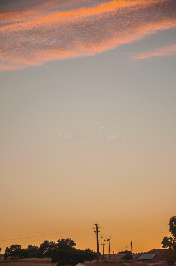 Nubes y cielo multicolores en la puesta del sol en una granja imágenes de archivo libres de regalías