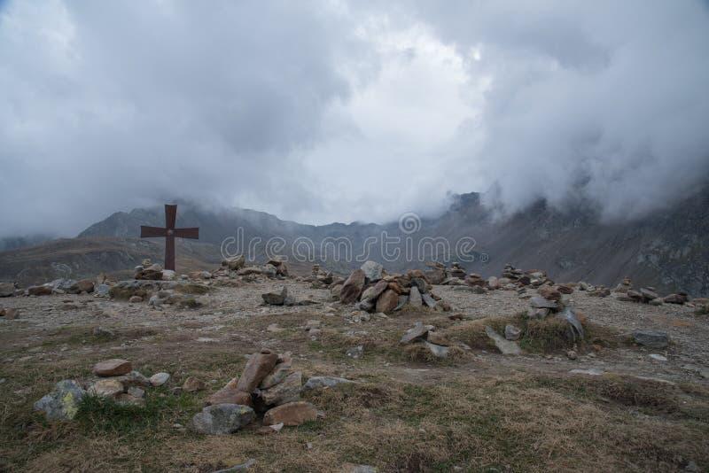 Nubes y cruz en las montañas foto de archivo