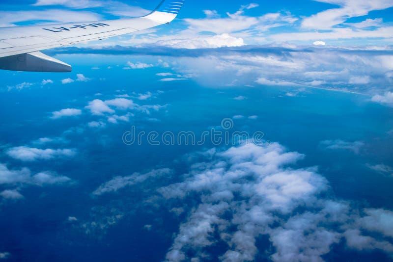 Nubes y orilla vistas desde arriba del avión de la ventana foto de archivo