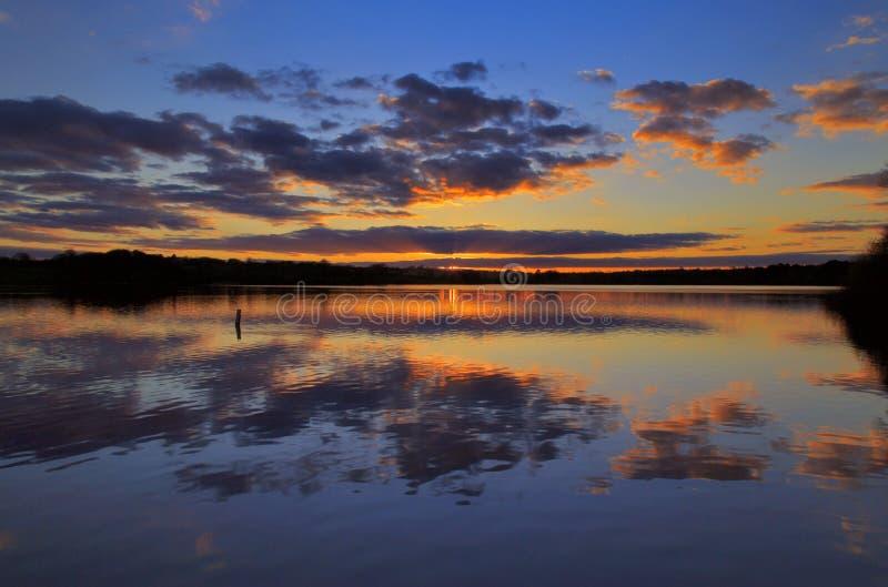 Nubes y puesta del sol reflejadas en agua inmóvil imágenes de archivo libres de regalías