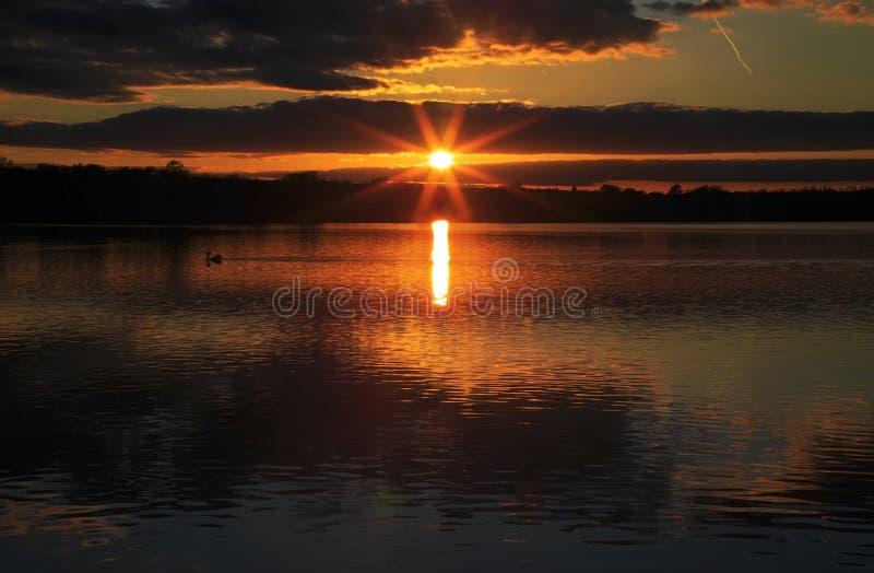 Nubes y puesta del sol reflejadas en agua inmóvil foto de archivo