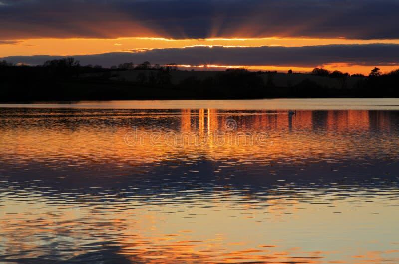 Nubes y puesta del sol reflejadas en agua inmóvil fotografía de archivo