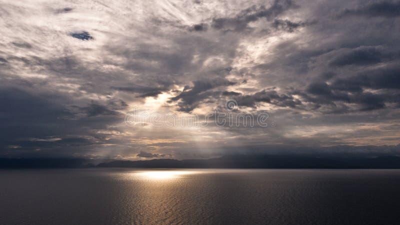 Nubes y rayos del sol sobre el mar Luz brillante con los rayos del sol y las nubes pesadas sobre el mar Cielo dram?tico imágenes de archivo libres de regalías