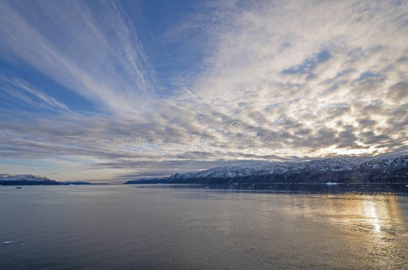 Nubes y Sun de la tarde en un alto fiordo ártico fotos de archivo libres de regalías