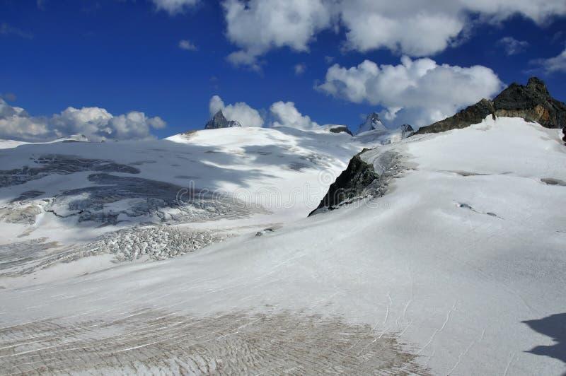 Nubi sopra il ghiacciaio ed il matterhorn fotografia stock