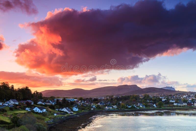 Nubi variopinte al tramonto sopra un villaggio fotografie stock libere da diritti
