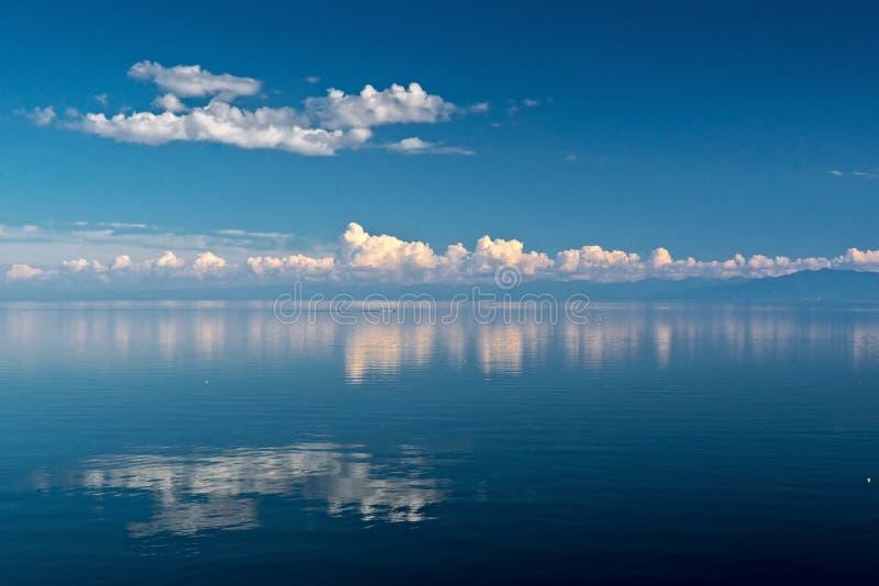 Nubla-se a reflexão na água do Lago Baikal imagem de stock