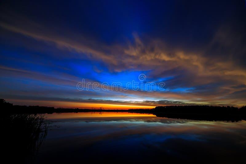 Nuble-se no alvorecer iluminado céu da manhã, refletido na água imagens de stock royalty free