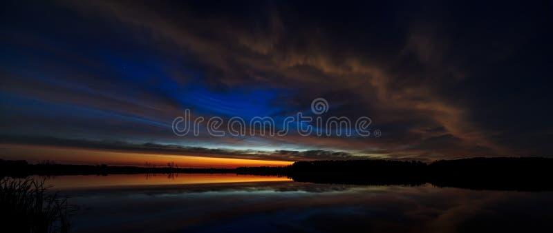 Nuble-se no alvorecer iluminado céu da manhã, refletido na água imagem de stock royalty free