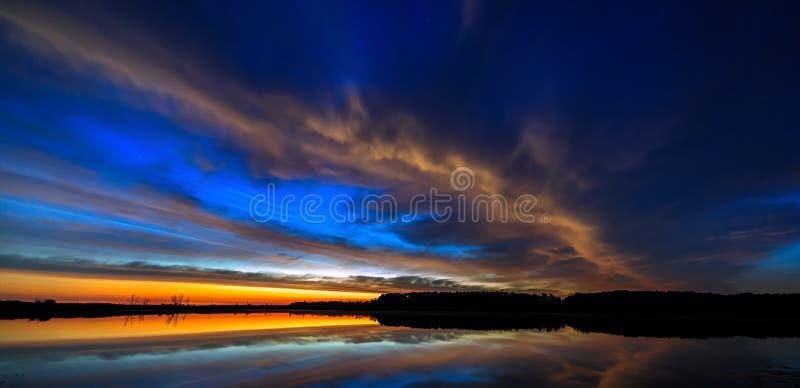 Nuble-se no alvorecer iluminado céu da manhã, refletido na água fotografia de stock