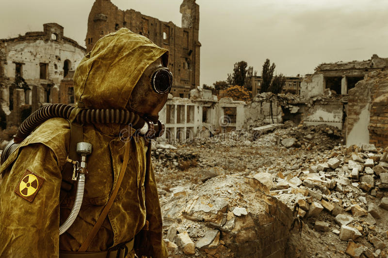 Nuclear apocalypse survivor. Post apocalypse. Sole survivor in tatters and gas mask on the ruins of the destroyed city stock photo