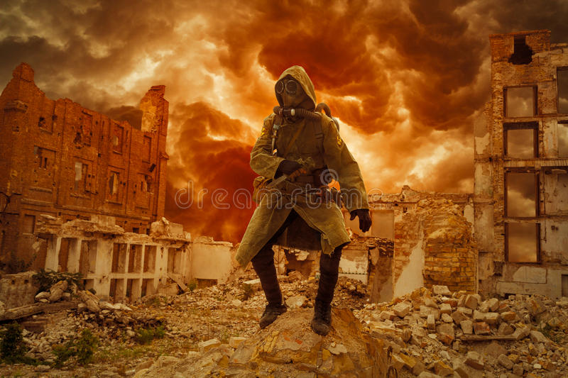Nuclear apocalypse survivor. Post apocalypse. Sole survivor in tatters and gas mask on the ruins of the destroyed city royalty free stock images