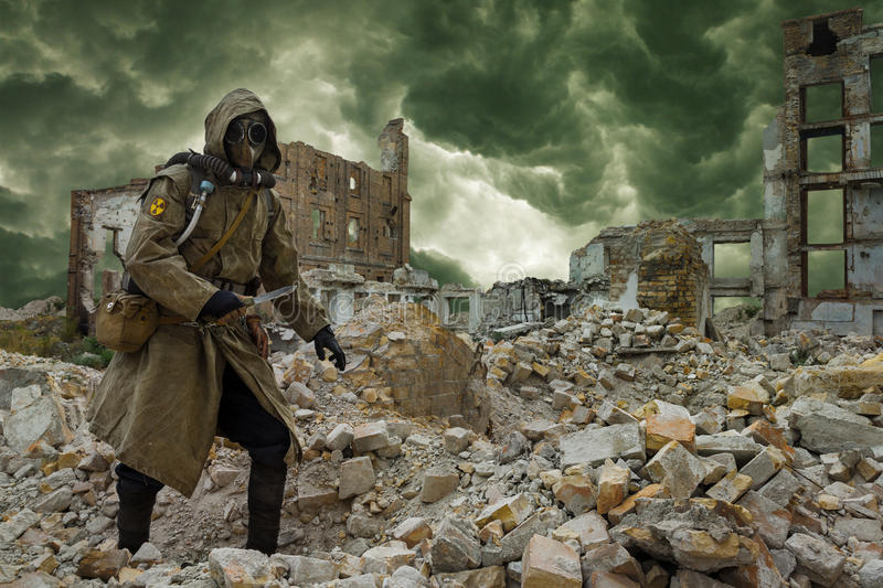 Nuclear apocalypse survivor. Post apocalypse. Sole survivor in tatters and gas mask on the ruins of the destroyed city royalty free stock image
