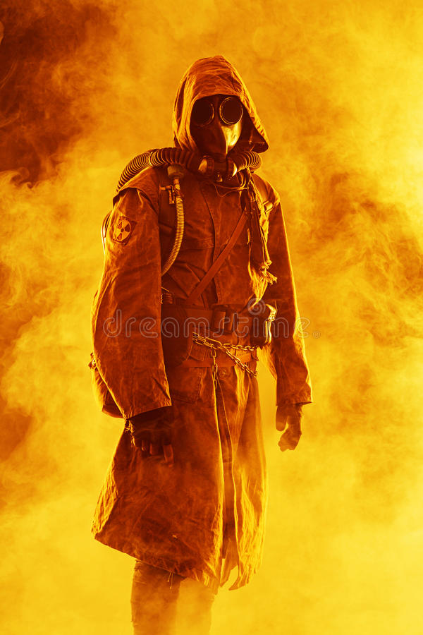 Nuclear post apocalypse. Studio shot of survivor in tatters and gas mask stock photo