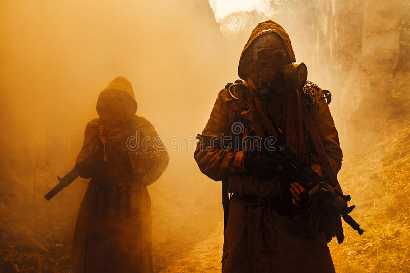 Nuclear post-apocalypse survivors. Nuclear post-apocalypse. Survivors in tatters and gas mask on the ruins of the destroyed city stock photography