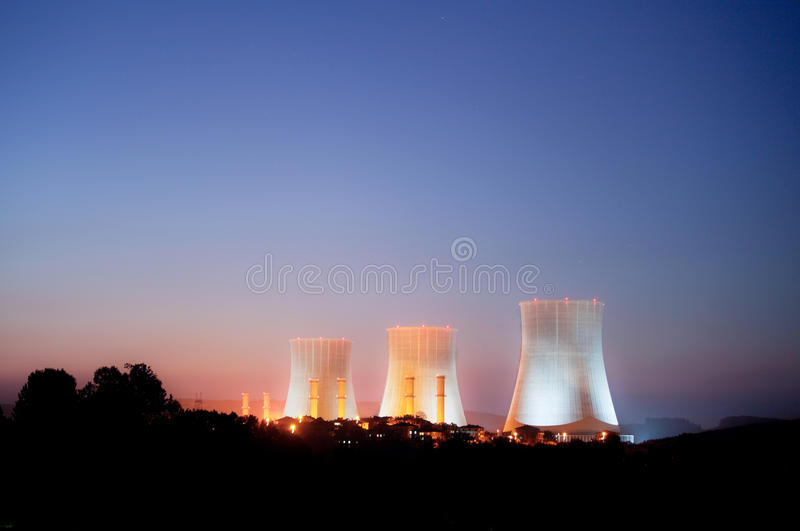 Nuclear power plant. A night time commercial scene of three large cooling towers at a nuclear power station royalty free stock photos