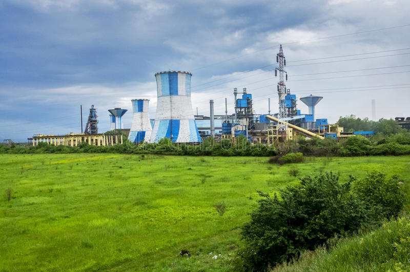 Nuclear power plant. In sunny day.  in from of a green meadow on a cloudy day royalty free stock photos