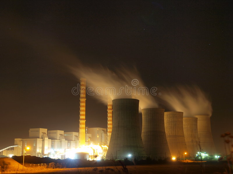 Nuclear power plant. The view of a nuclear power plant with many cooling towers and chimneys, lit up at night stock photos